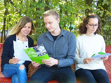Drei Studenten sitzen auf der Bank und lesen HTW-Berlin Broschüre